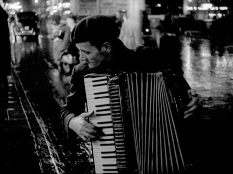 a busker plays an accordian next to a cinema on leicester square - bbc archive stock-videos und b-roll-filmmaterial