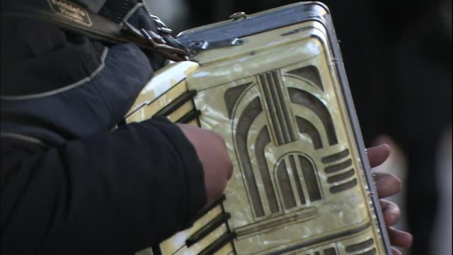 vídeos y material grabado en eventos de stock de a busker plays the accordion on a busy sidewalk in helsinki, finland. - acordeonista
