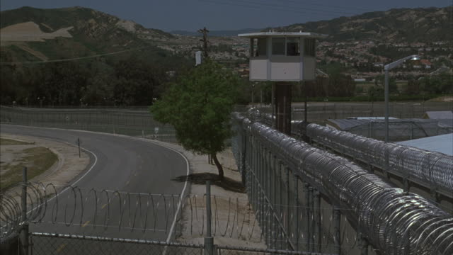 A busload of prisoners with a police escort arrive at the Santa Clarita Prison.