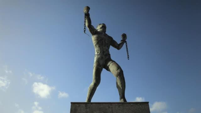 vídeos de stock e filmes b-roll de ws la bussa emancipation statue, leader of slave uprising in barbados / haggatt hall, st michael, barbados - the machine: master or slave
