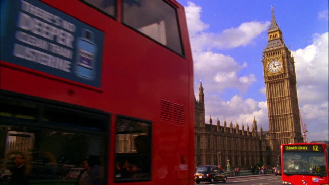 slo mo ms busses on westminster bridge, houses of parliament and big ben in background, london, england - autobus a due piani video stock e b–roll