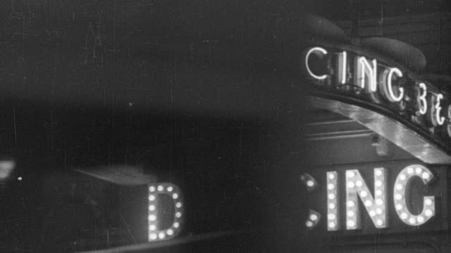 1940 MONTAGE Bustling pre-war night life in the West End, with pedestrians and vehicle traffic driving past, and outdoor lighting signs for businesses / London, England, United Kingdom
