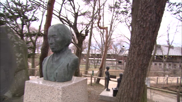 Busts mounted on plinths border a park in Japan.
