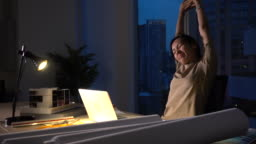 Busy Asian Woman Working in Dark Office at Night
