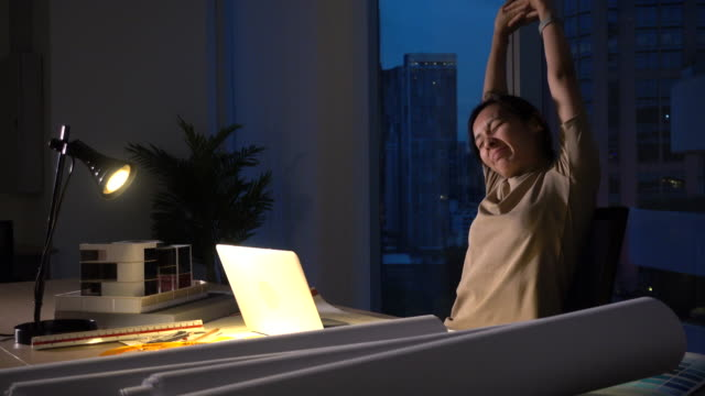 busy asian woman working in dark office at night - stretching stock videos & royalty-free footage
