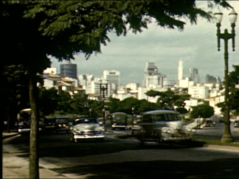 vidéos et rushes de os busy boulevard in sal paolo skyscrapers in background goodyear sign in foreground / ms buses and cars drive by / pan over tall buildings in city... - sao paulo