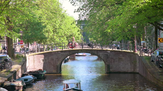 busy bridge in amsterdam with bicycles, boats and people - 北ホラント州点の映像素材/bロール