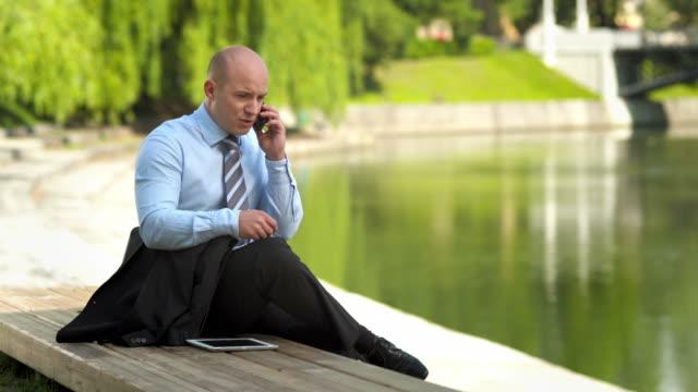 vídeos de stock e filmes b-roll de hd: empresário ocupado pelo rio da cidade - camisa e gravata