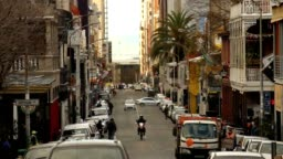 Busy Cape Town street, late afternoon, filled with cars, pubs and people