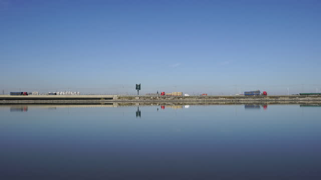 busy cargo transportation on the highway, reflected in the lake in tianjin, china on november 2, 2020. - fast motion stock videos & royalty-free footage