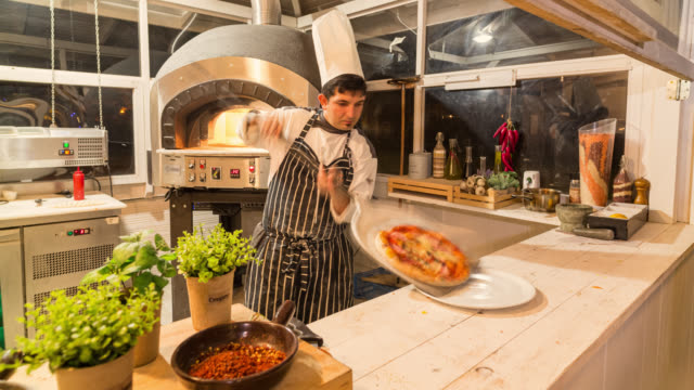 busy chef and pizzaiolo in his kitchen in front of pizza oven prepares pizza, meat and fish dishes. - preparation stock videos & royalty-free footage
