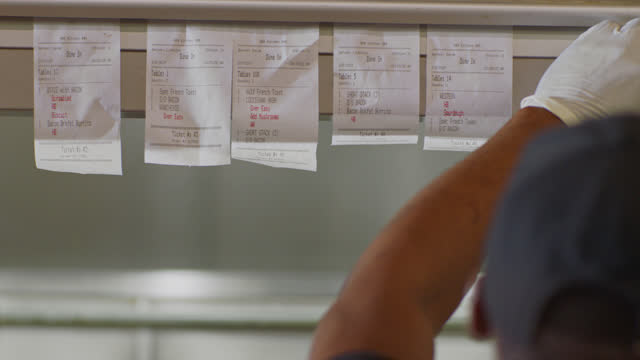 slo mo. cu a busy chef slides an order ticket down on a restaurant ticket holder in a commercial kitchen - receipt stock videos & royalty-free footage