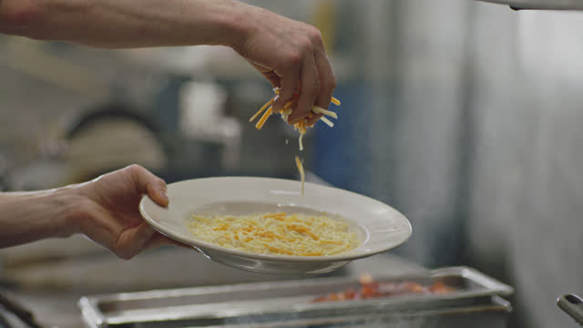 slo mo. cu of busy chef sprinkling cheese onto grits on a white plate in an authentic diner - チーズ点の映像素材/bロール