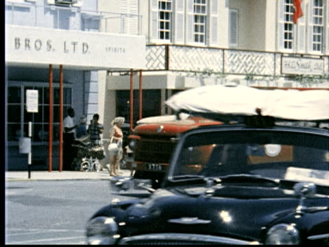 1963 ws busy city street in hamilton with traffic. red tan truck with sun tan lotion on side / hamilton, bermuda - bermuda stock videos & royalty-free footage