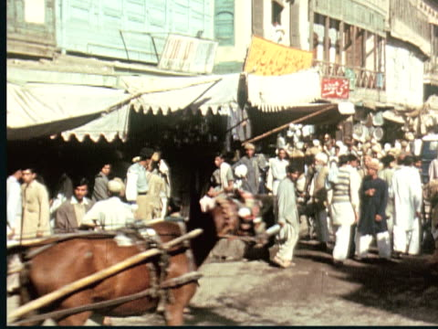 vídeos de stock e filmes b-roll de 1960 montage busy city street market with horse carts. man carries large basket on head. man sells carpets in street. shops with fabrics / pakistan - paquistão