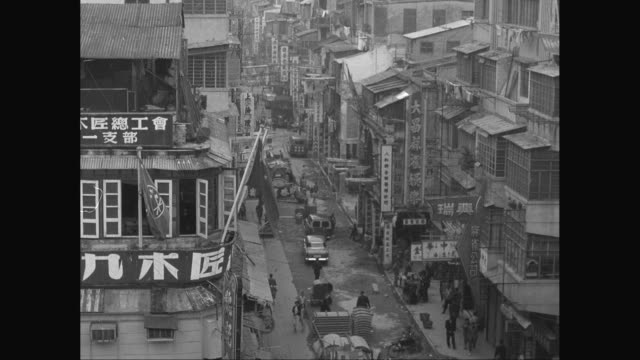 ws ha busy city street with many signs on buildings, pedestrians, cars on street / japan - 1950~1959年点の映像素材/bロール