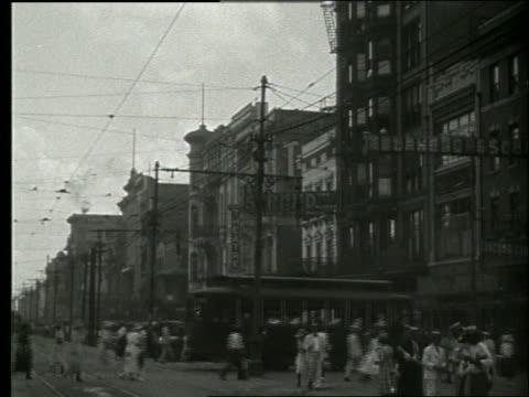 vidéos et rushes de b/w busy city street with people and trolleys / new orleans / 1915 / no sound - la nouvelle orléans