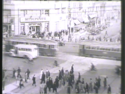 stockvideo's en b-roll-footage met busy city streets of tokyo including pedestrians some in kimonos automobiles trolleys on cross streets buildings including 'tokyo asahi' 'mitsukoshi'... - 1942
