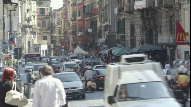 ms zo busy cobblestone street in naples with heavy daytime traffic / naples, campania, italy - ナポリ点の映像素材/bロール