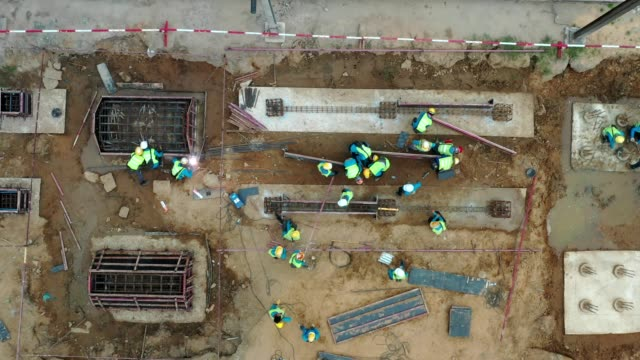 busy construction job site, aerial view, many men, worker working at civil site - construction material stock videos & royalty-free footage