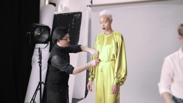 busy crew working on a fashion photoshoot in studio - ディレクター点の映像素材/bロール
