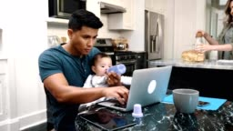 Busy dad feed his baby girl while using laptop
