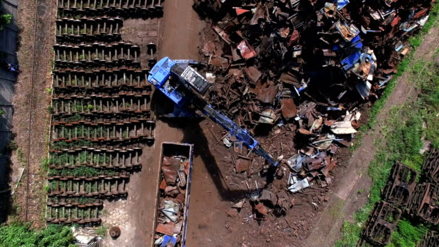 busy day at junkyard. mechanical claw drops metal scrap. aerial view - heap stock videos & royalty-free footage