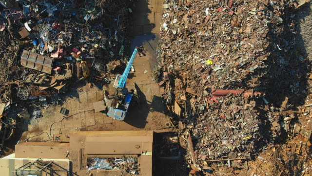 busy day at junkyard. mechanical claw drops metal scrap. aerial view - metal stock videos & royalty-free footage
