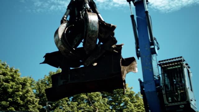 vídeos de stock e filmes b-roll de busy day at junkyard. mechanical claw drops metal scrap - guindaste maquinaria de construção