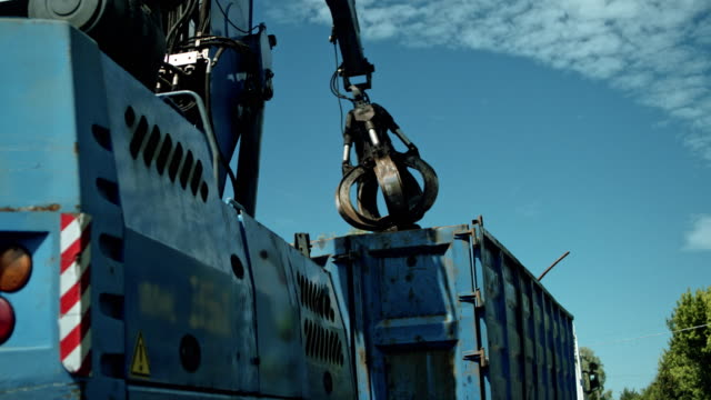 busy day at junkyard. mechanical claw drops metal scrap - steel stock videos & royalty-free footage