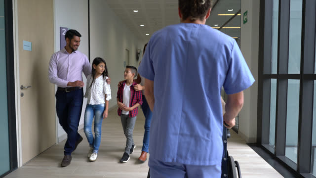 busy day at the hospital, patients and healthcare staff walking through the corridor - building entrance stock videos & royalty-free footage