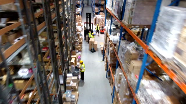 Busy day at warehouse. Worker driving on a forklift. Drone point of view