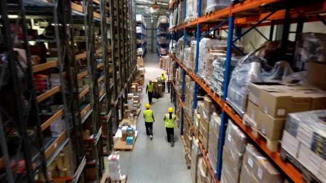 倉庫で忙しい一日。パレット ジャッキを使用してワーカー。ドローンの視点 - 倉庫作業員点の映像素材/bロール