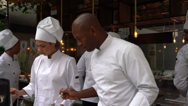 busy diverse team of cooks and chef preparing food at the restaurant's kitchen - african american ethnicity stock videos & royalty-free footage