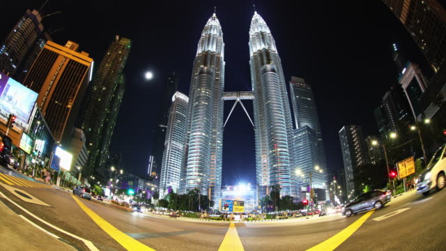 a busy evening at the foothills of iconic petronas twin towers - kuala lumpur, malaysia - petronas twin towers stock videos & royalty-free footage