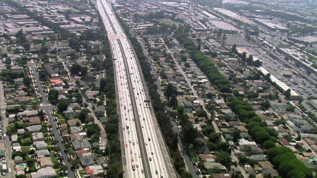 AERIAL A busy expressway, full of fast moving vehicles and surrounded by urban sprawl / California, United States