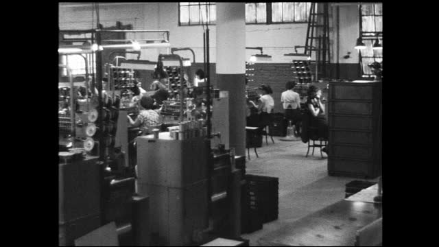 vidéos et rushes de busy factory floor full of women workers assembling parts; other people walks by - 1940 1949