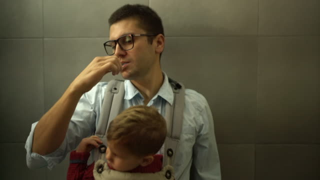 vídeos de stock e filmes b-roll de busy father brushing his teeth - multitarefas