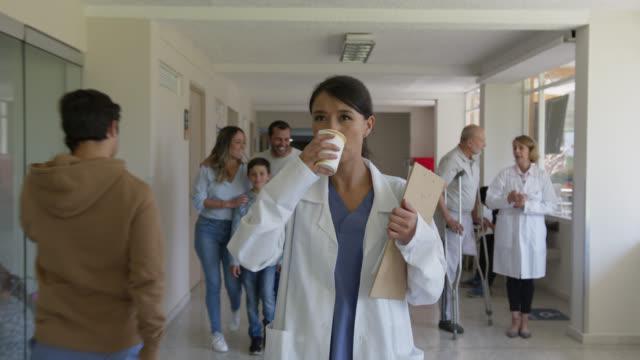 病院の廊下を歩きながら医療チャートを見て、コーヒーを飲む忙しい女性医師 - 飲み物点の映像素材/bロール