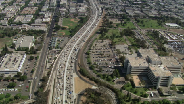 vídeos de stock, filmes e b-roll de aerial busy freeway stretching beyond urban sprawl / los angeles, california, united states - formato letterbox