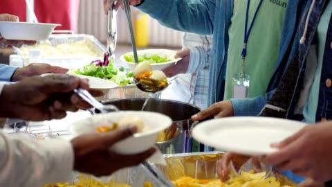 busy group of volunteers serving community in soup kitchen - volunteer stock videos & royalty-free footage