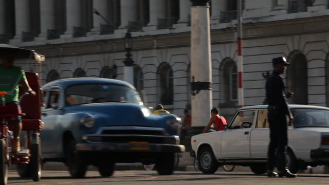 WS, busy Havana street with vintage American cars and pedestrians