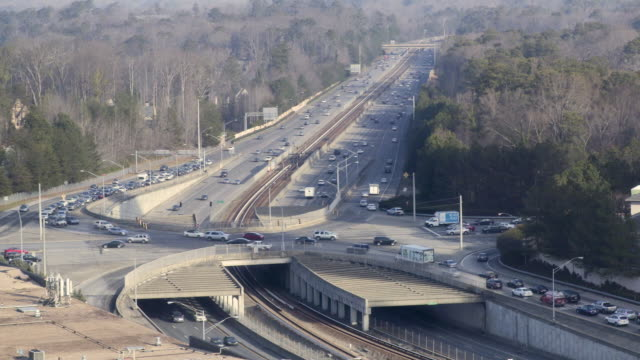 Busy highway interchange with subway train in the middle