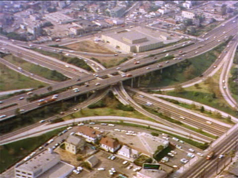 1962 AERIAL busy highway with overpasses + ramps in suburban area / industrial