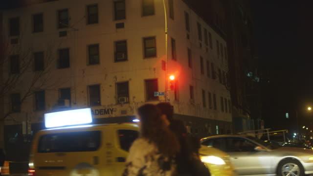 Busy intersection at night in the East Village, New York City