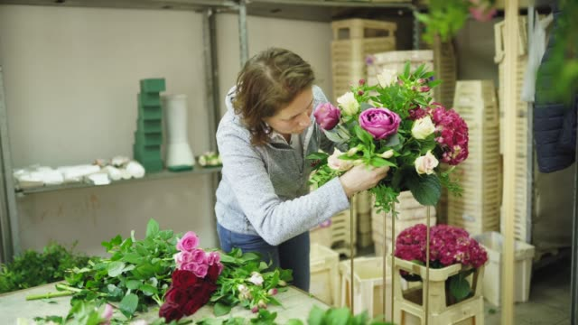 busy ladies making floral arrangement in workshop together - bouquet stock videos & royalty-free footage