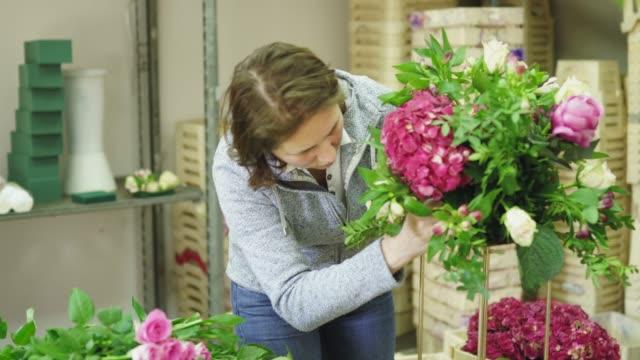 vidéos et rushes de femme occupée fleuriste travaillant dans l'atelier de fleur seul - bouquet de fleurs