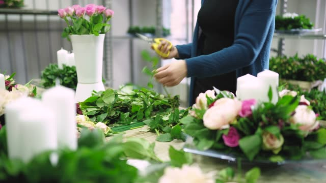 Busy lady florist working in flower workshop