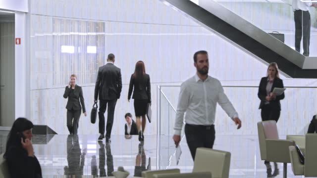 vídeos de stock, filmes e b-roll de ld movimentado lobby do edifício corporativo - característica de construção