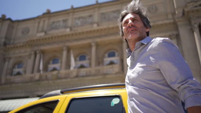 imprenditore maschio impegnato che esce da un taxi - tourism video stock e b–roll
